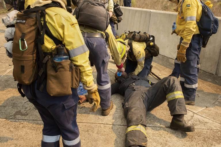 رجال الإطفاء يحاولون إفاقة زميل لهم اختنق الدخان والحرارة